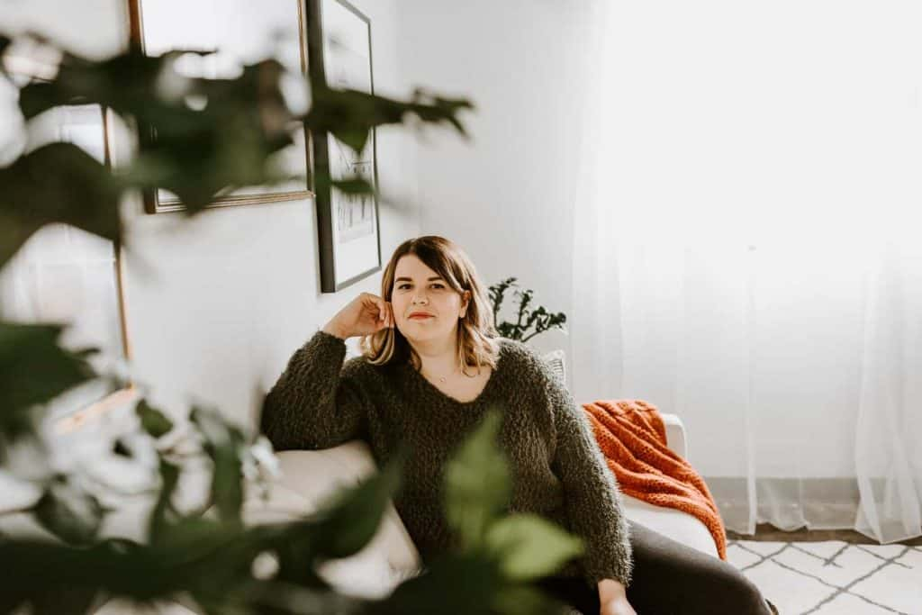 Girl wearing green sitter sitting on couch looking through tree