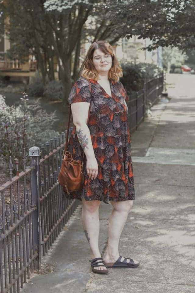 A girl in a dress looking down wearing a leather bag