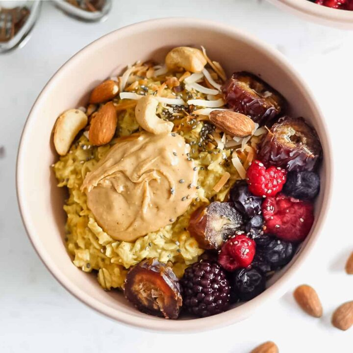 A bowl of vegan oatmeal topped with fresh berries and nut butter