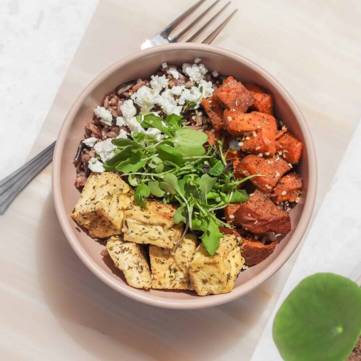 A bowl with rice, marinated baked tofu, sweet potato, goat cheese, and microgreens