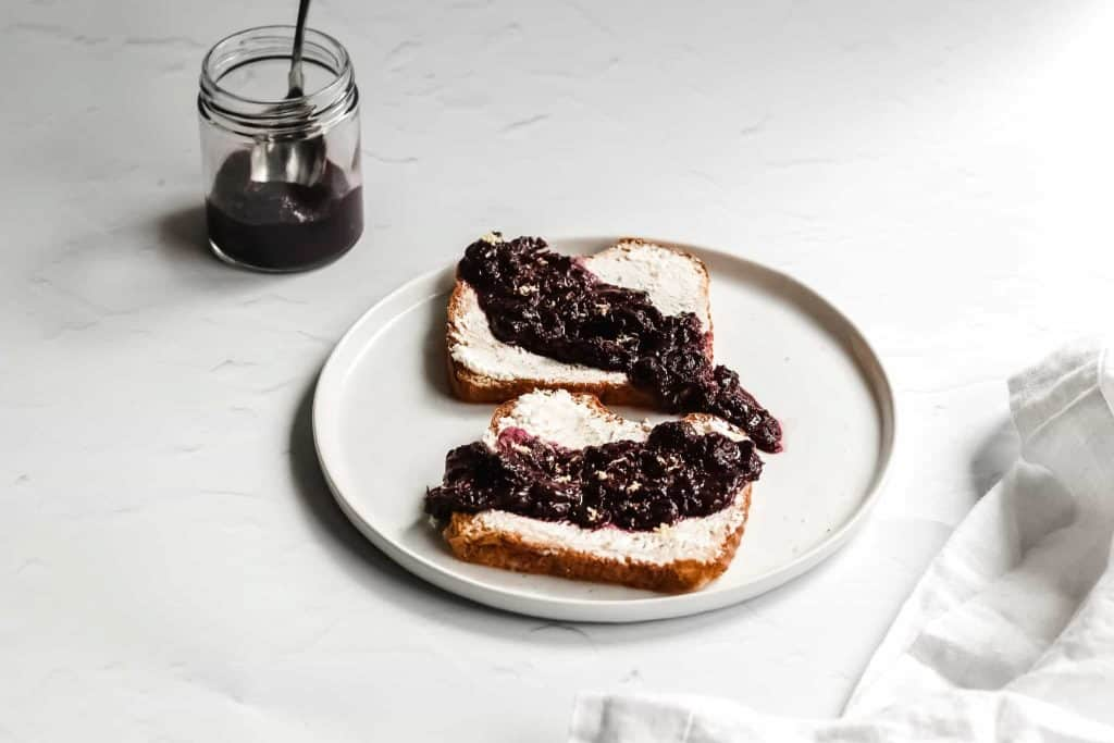 A completed healthy blueberry compote recipe for pancakes. Here, the fresh blueberry compote is on toast with goat cheese. Fresh blueberry sauce is in a jar behind the toast. A spoon is in the jar of cooked blueberries that has turned into blueberry sauce. This lemon blueberry compote recipe is delicious.