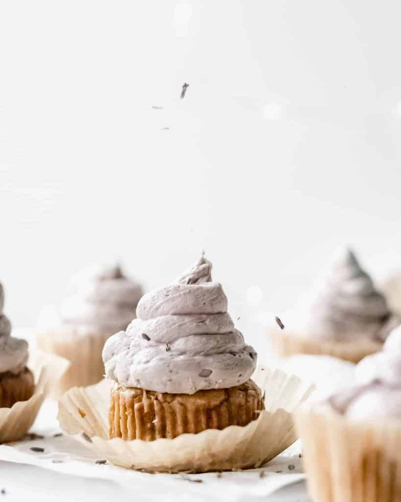 A gluten free lemon lavender cupcake with purple icing on a table with other cupcakes behind it. Lavender is being dropped onto the cupcake