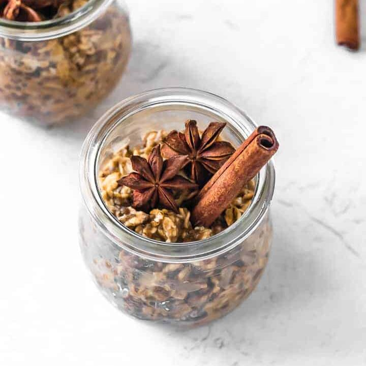 A glass jar filled with overnight oats with a cinnamon stick and star anise on top