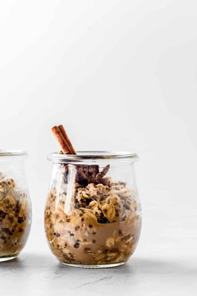 Chai tea overnight oats in a small jar with a cinnamon stick and star anise inside the jar