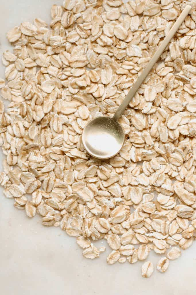 Raw oats with a golden metal spoon on top of them