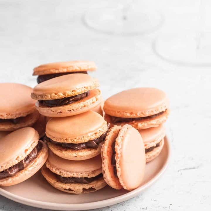 Orange macarons with chocolate buttercream stacked on a pink plate