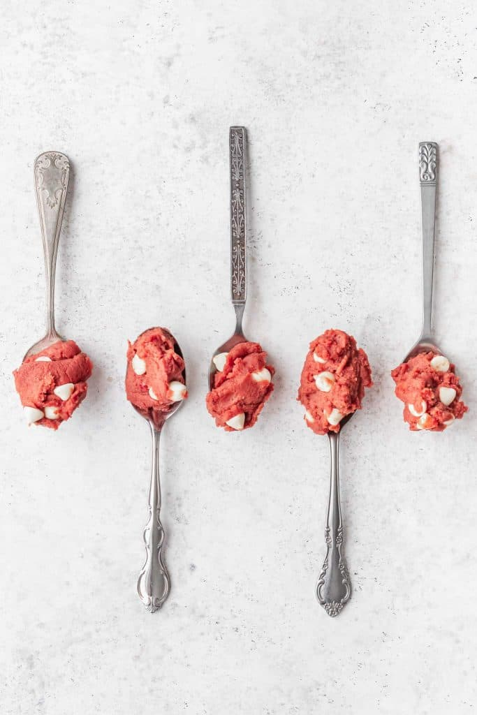 Five antique spoons with red cookie dough in each one