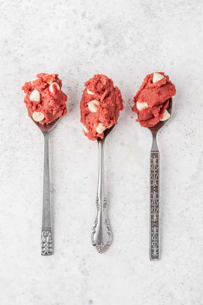 Three spoons with red velvet cookie dough