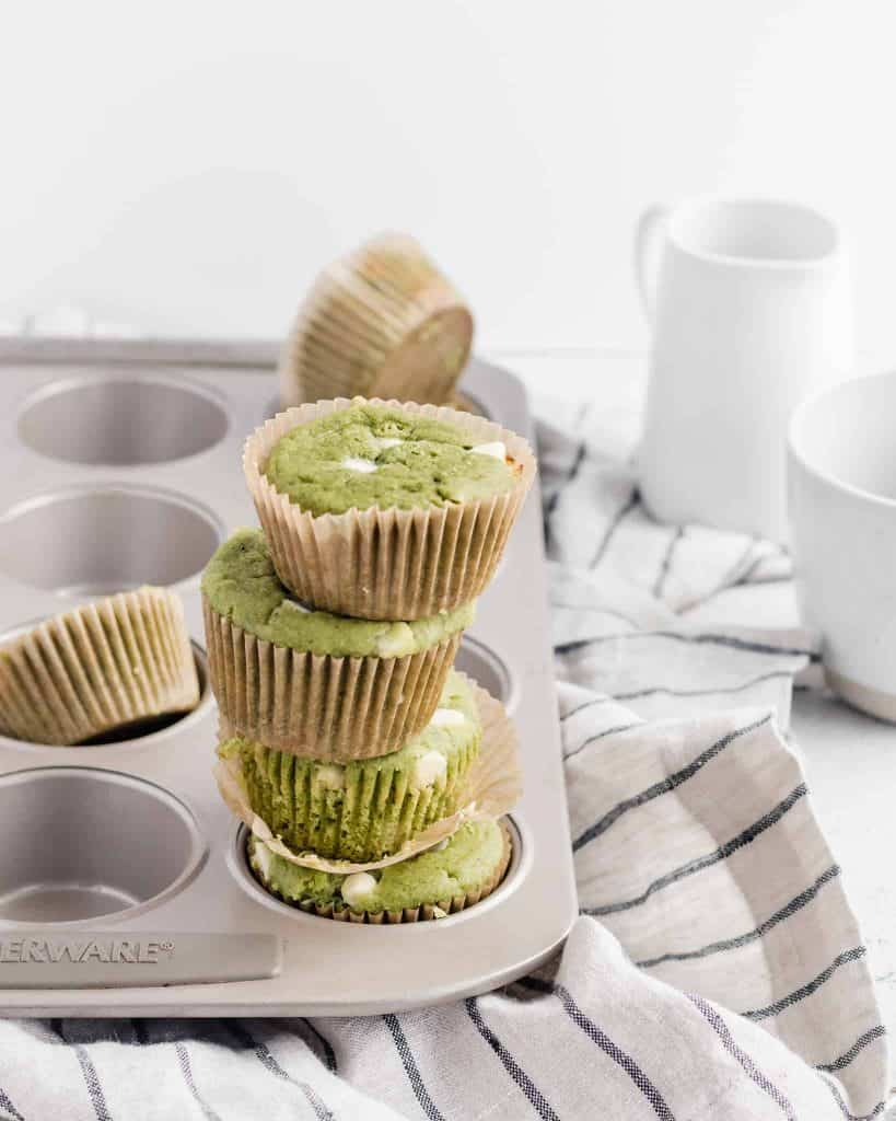 Gluten free white chocolate matcha muffins stacked in a muffin tin on a striped napkin