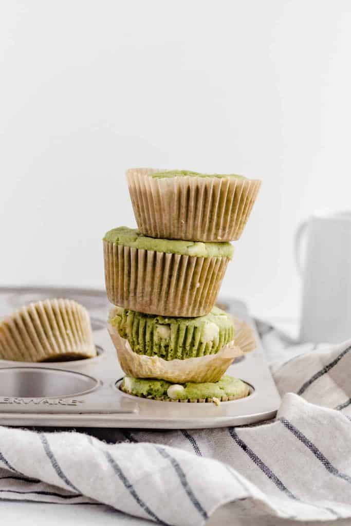 White chocolate matcha gluten free muffins stacked in a muffin baking pan