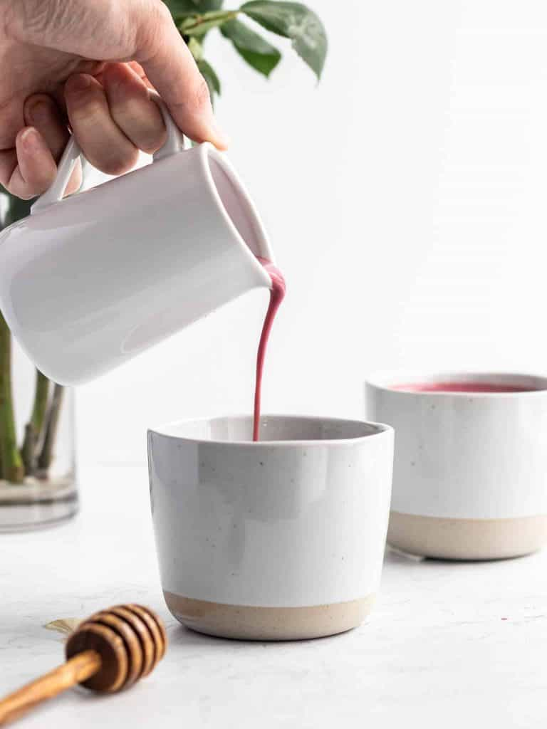 Two mugs next to each other with pink moon milk being poured into one of the mugs