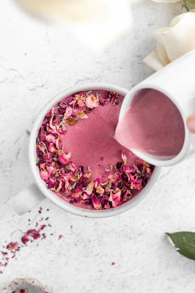 Pouring rose beetroot pink moon milk into a mug