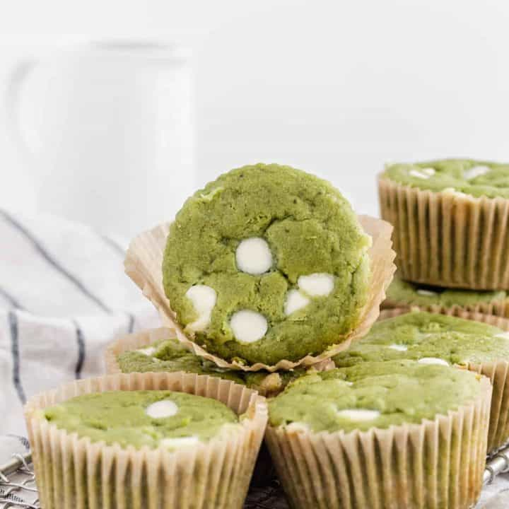 White chocolate matcha muffins stacked on top of each other on a white and blue striped napkin