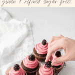 six chocolate blackberry cupcakes on a cooling rack with hand grabbing one of them